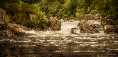 A photograph of water rushing over the rocks heading towards the River Coe in Glencoe, Scotland