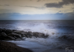 A photography of waves hitting rocks at sidmouth