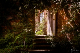 A wooden gate leading you to courtyard at Sissinghurst Gardens
