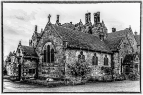 A monochrome photograph of the main house at Wakehurst Place.