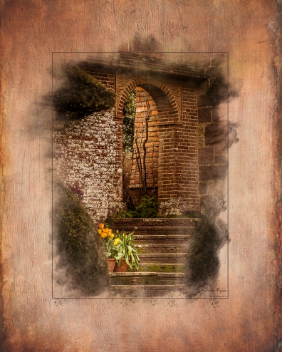 A photograph of a brick arch taken at Great Dixter House and Gardens.