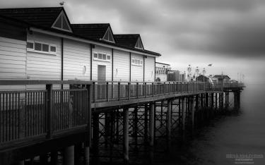 A monochrome photograph of a pier along the South Coast of England.