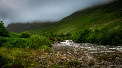 A photograph of the River Coe at Glencoe in Scotland, photographed on a stormy day with low cloud.