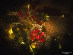 A photograph of a gold bell, cone and berry christmas decoraiton.