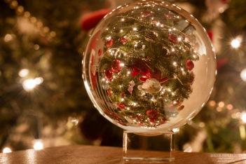 A photograph of a Santa tree ornament photographed through a crystal ball