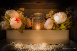 A still life photograph of peonies, beads and a candle in a jar.