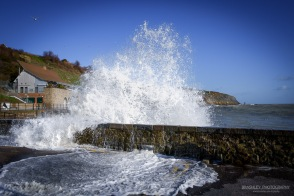 A photograph of one of the waves crashing over the sea wall at Folkestone in Kent on a windy day.