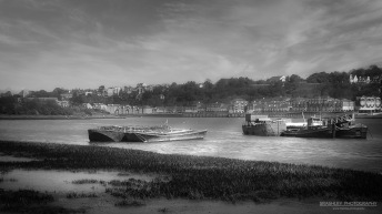A monochrome photograph of barges on the River Medway, at Medway Valley in Kent.