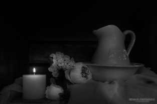 A monochrome photograph of a china wash jug and bowl with flowers and candle.
